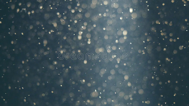 Abstract blue background with beautiful golden flickering particles. Underwater bubbles in flow with bokeh royalty free stock image