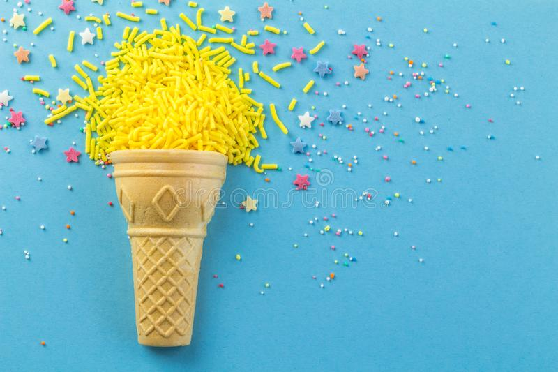 Abstract blue background with wafer cone and yellow cake topping sprinkles scattered - top view photo with copy space. Abstract blue background with wafer ice royalty free stock photography