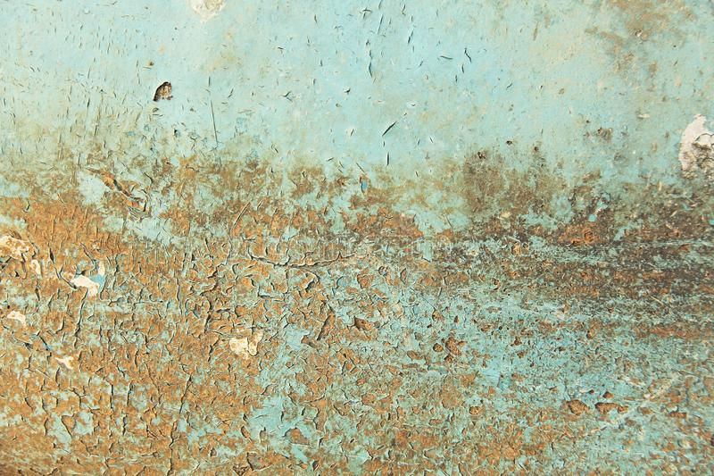 Abstract blue, beige and turquoise background wallpaper texture. Old flaky paint peeling off grungy cracked wall. Cracks, scrapes, peeling old paint and stock photo