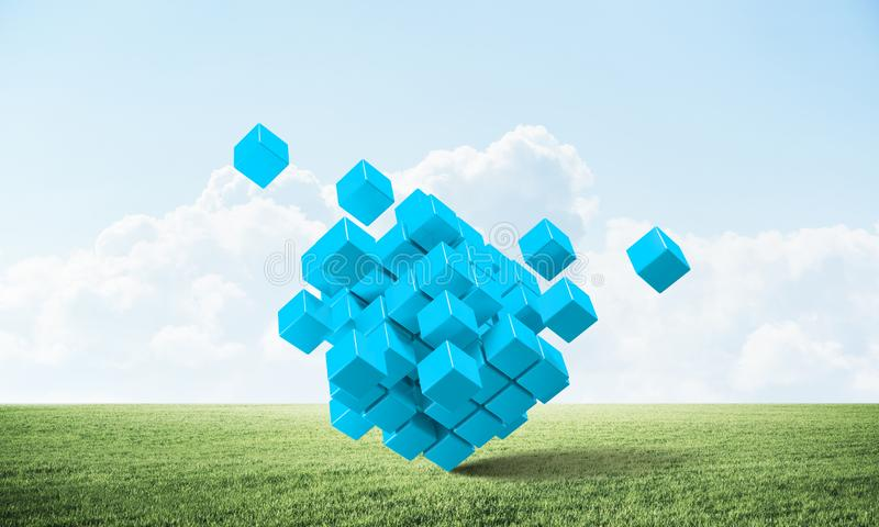 Abstract blue cubes on green meadow stock images