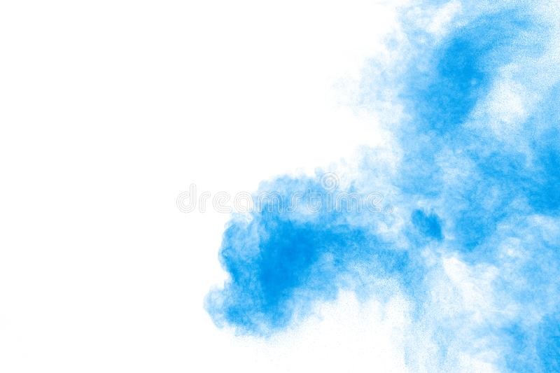 Abstract blue dust explosion on white background. Freeze motion of blue powder splash. Painted Holi in festival.  royalty free stock image