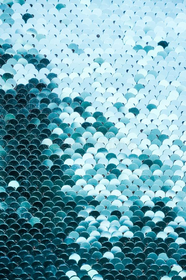 Abstract blue Texture with bright Sequins . Glamor scales Background with shiny Sequins on fabric. Beautiful Holiday stock photography