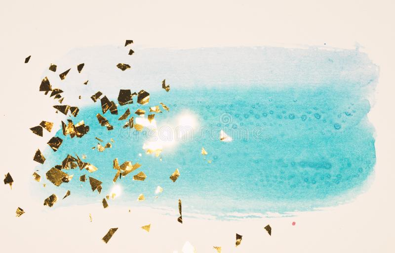 Abstract blue watercolor splash and golden glitter, pieces of foil, background in vintage nostalgic colors. royalty free stock photo