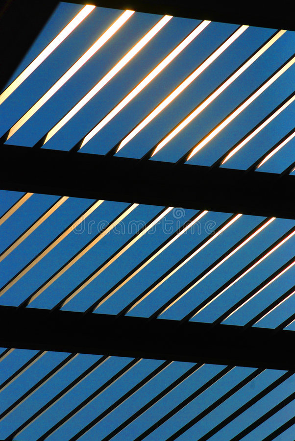 Abstract bluish background. An abstract, bluish background with repeating lines created by a closeup of overhead steel beams in the lattice work of a pergola royalty free stock photography