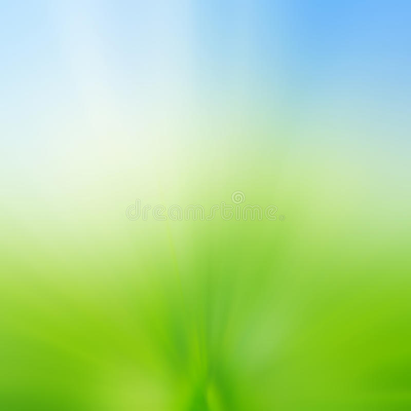 Abstract blur background of green grass field and blue sky above royalty free stock photography