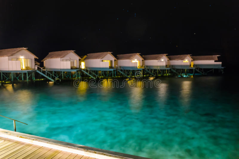 Abstract blur Milky Way over water villa cottages on Maldives . royalty free stock photos