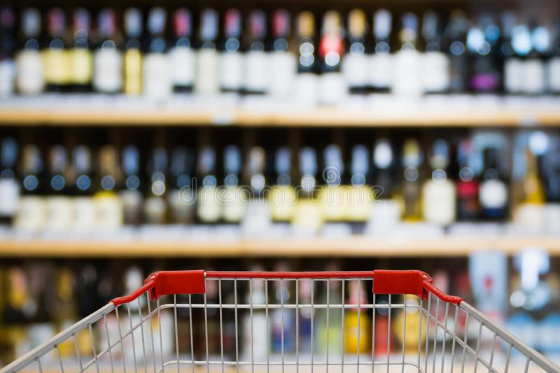 Abstract blur wine bottles on liquor alcohol shelves. Shopping cart view with Abstract blur wine bottles on liquor alcohol shelves in supermarket or wine store royalty free stock photo