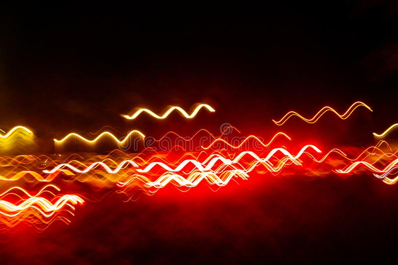 Abstract blurred colorful light effect on a black background. Long exposure photo of moving camera.  royalty free stock photography