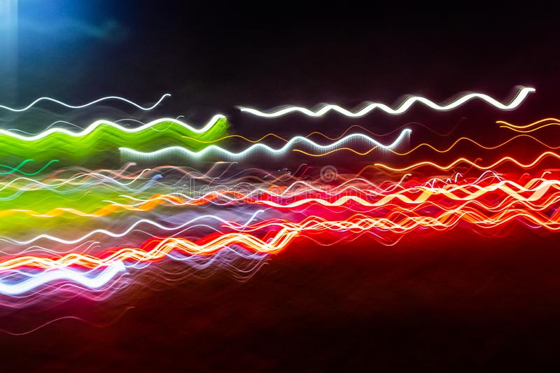 Abstract blurred colorful light effect on a black background. Long exposure photo of moving camera.  royalty free stock photo