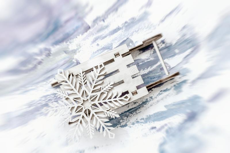 Abstract blurred festive Christmas background. Wooden decoration, snowflake on little wooden sled. Abstract blurred festive light Christmas background. Wooden royalty free stock images
