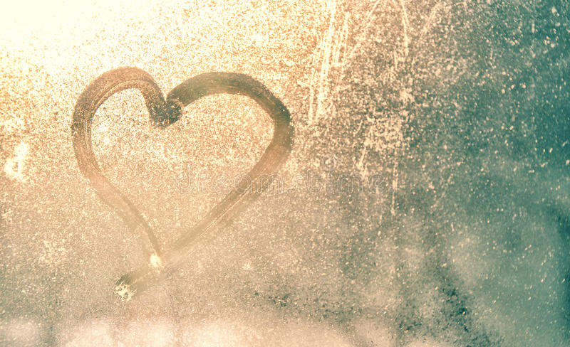 Abstract blurred heart shape on frozen window. Abstract blurred love heart symbol drawn by hand on the wet, frozen and dirty window glass with yellow gold stock image
