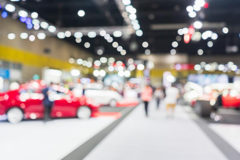 Abstract blurred image of cars exhibition show. Blurred defocused image of public event exhibition hall showing cars and. Automobiles, business commercial stock images