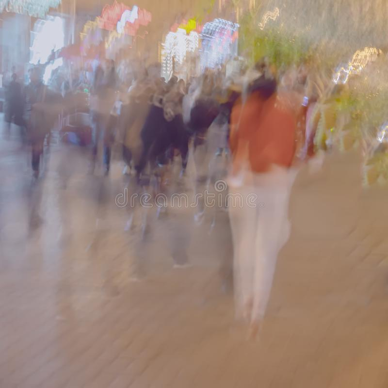 Abstract blurred image of unrecognizable silhouettes of people walking in city street in evening, shopping. Urban modern stock photography