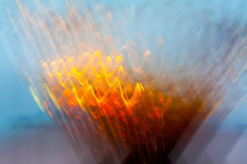 Abstract blurred light effect of orange waves on a blue background. Long exposure photo of moving camera.  stock image
