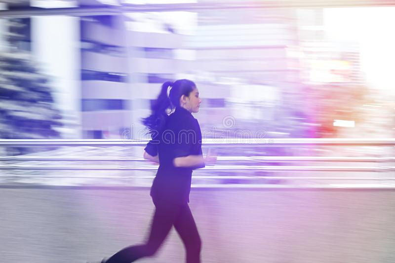 Abstract blurred motion of young Asian business woma running to work with light effect. royalty free stock image