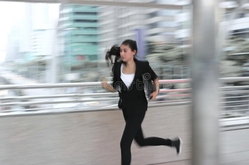 Abstract blurred motion of young Asian business woman running to work.  royalty free stock photos