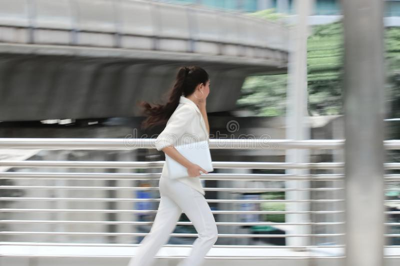 Abstract blurred motion of young Asian business woman running to work royalty free stock photo