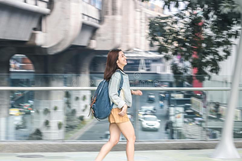 Abstract blurred motion of young Asian woman tourist running on street stock photography