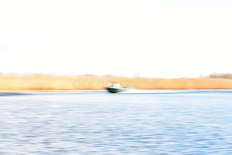 An abstract blurred out of focus image of a boat racing at speed. Along a river royalty free stock photo