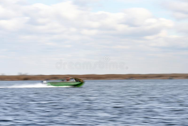 An abstract blurred out of focus image of a boat racing at speed. Along a river stock image