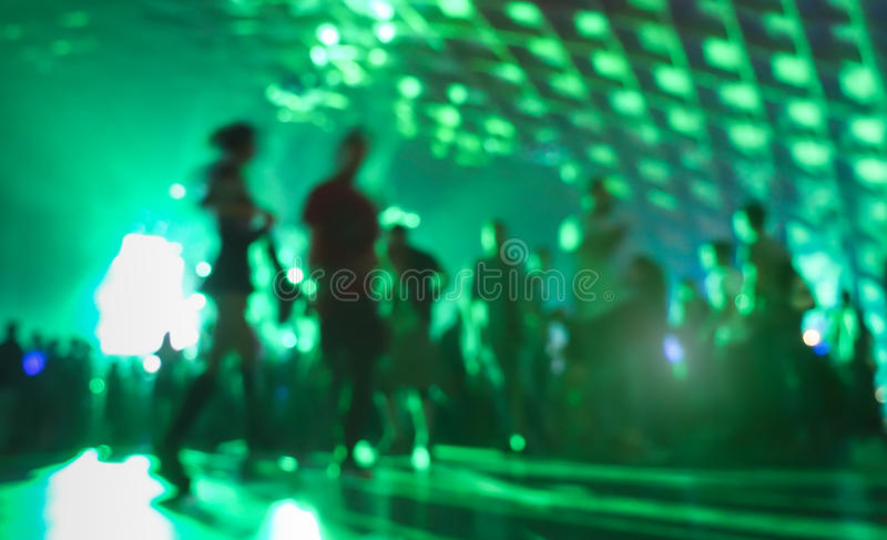 Abstract blurred people moving on and dancing at music club. Abstract blurred people moving on and dancing at music night festival event - Defocused image of stock photo