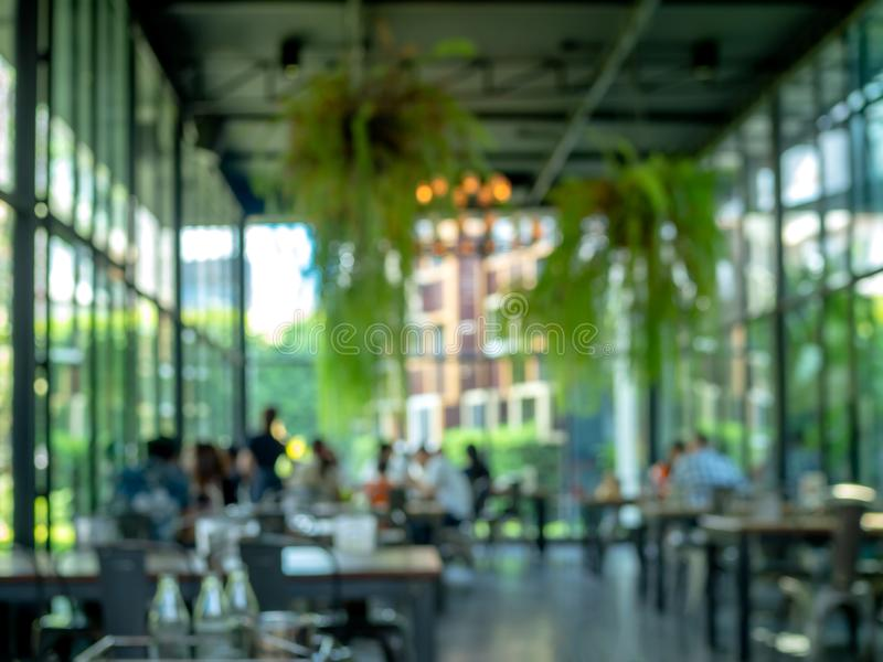 Abstract blurred people in restaurant or cafe decorate with hanging plant and window glass around the space royalty free stock images