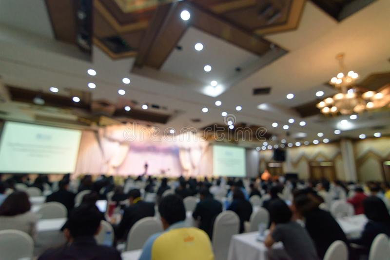 Abstract blurred photo background of business people in conference hall or seminar room. Defocused people in meeting room concept royalty free stock image