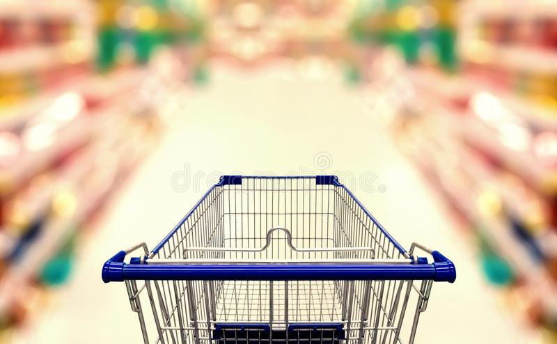 Abstract blurred photo of supermarket with empty shopping cart royalty free stock photos