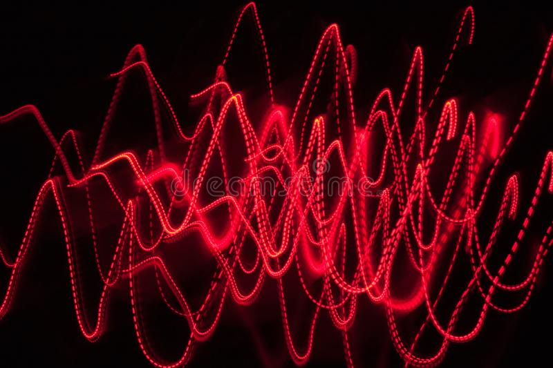 Abstract blurred red light effect on a black background. Long exposure photo of moving camera.  stock photography