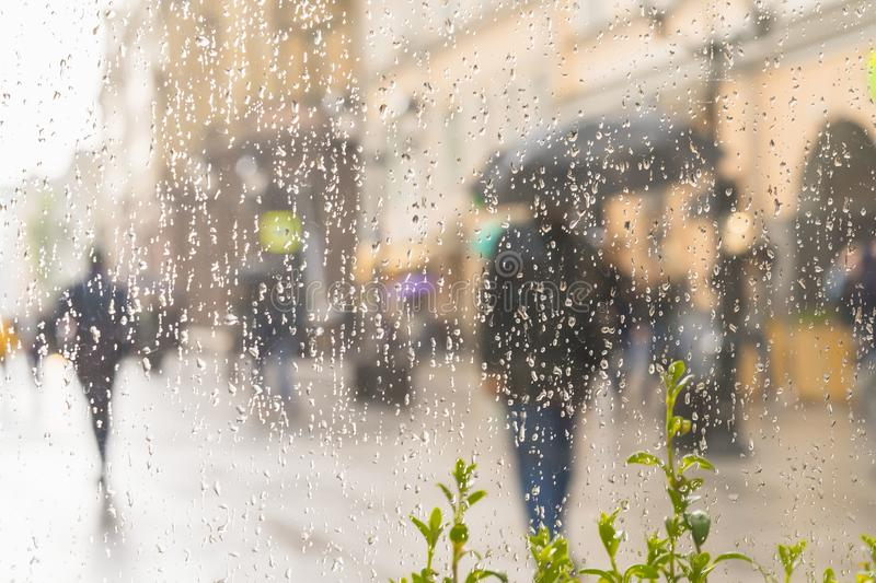 Abstract blurred silhouette of men under umbrella, city street seen through raindrops on window glass, blurred. Concept royalty free stock photos