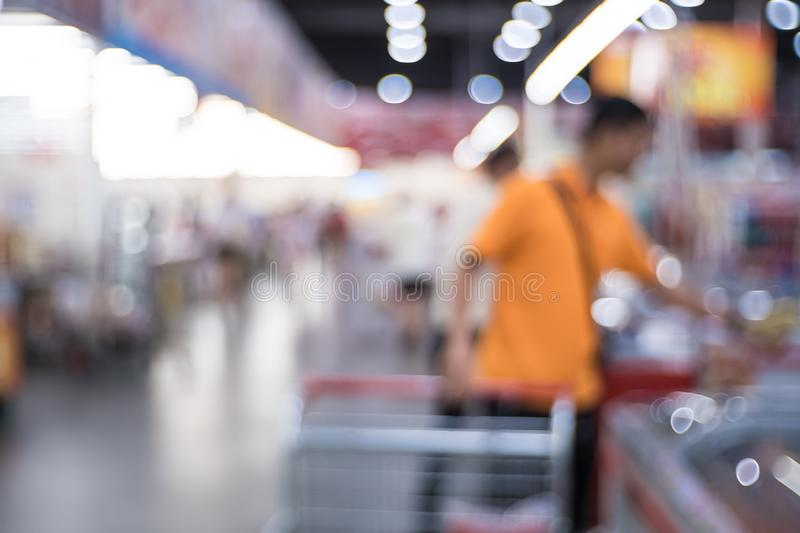 Abstract blurred supermarket aisle with colorful shelves and unrecognizable customers as background. stock photos
