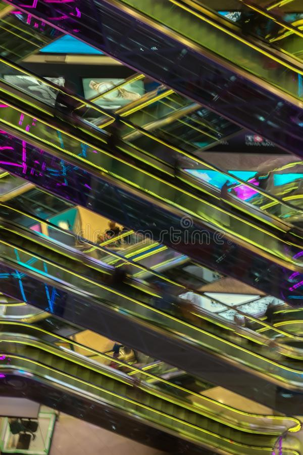 Abstract blurredn image of shopping mall, unrecognizable silhouettes of people on escalators with yellow backlight stock image