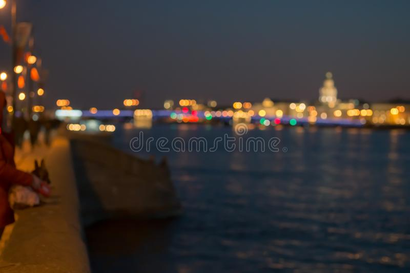 Abstract blurried lights over the night city river background. Beautiful sunset over Neva river of St. Petersburg, Russia royalty free stock images