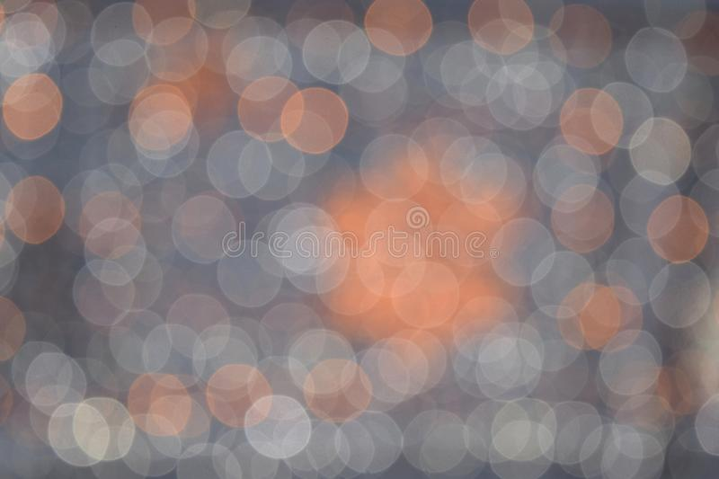 Abstract blurry background in orange and gray colors. Abstract white and orange bokeh circles lights that sparkle on a dark gray background stock photography