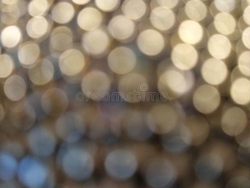 Abstract blurry circles from shining bulbs from a New Year`s garland. Yellow - gray colors stock images
