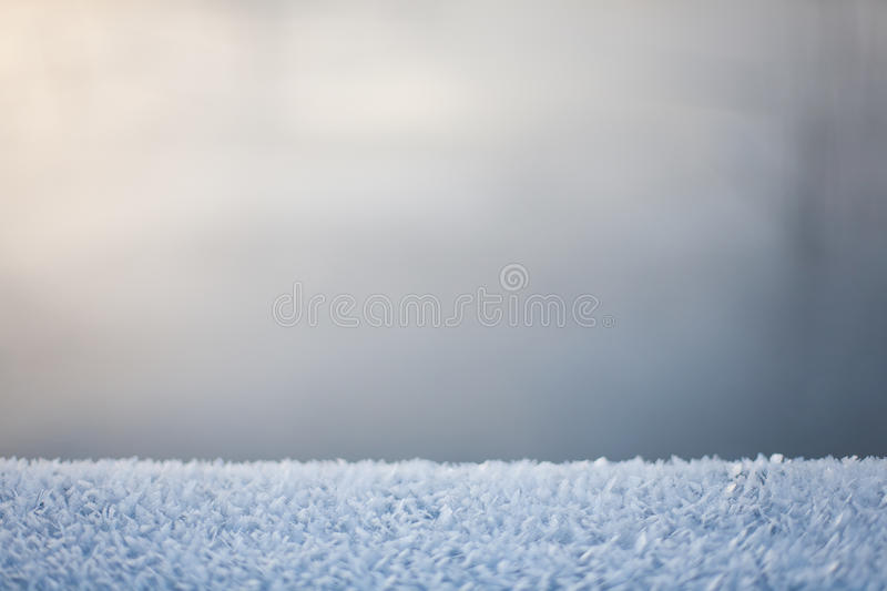 Abstract blurry frozen winter background with neutral colors. Abstract blurred winter frozen lake background with frost crystals on the foreground in pastel royalty free stock photography