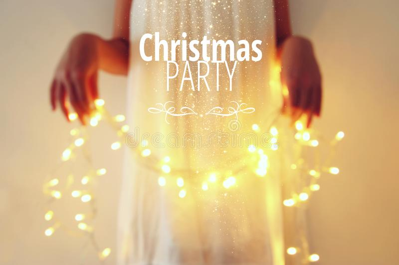 Abstract and bokeh image of young woman holding garland christmas lights and typography: CHRISTMAS PARTY. Holiday invitation conce royalty free stock photos