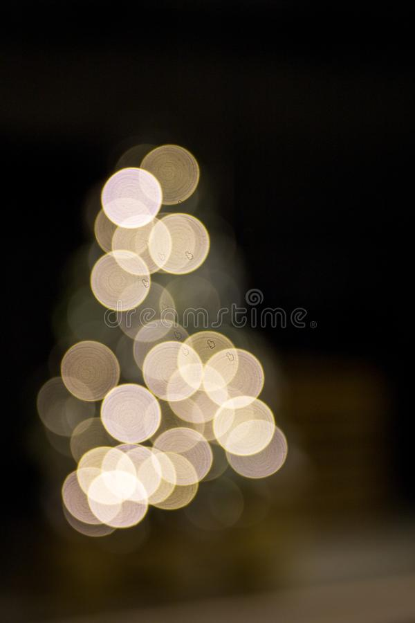 Abstract bokeh lights background in shape of Christmas tree. Festive concept. Place for design stock photo