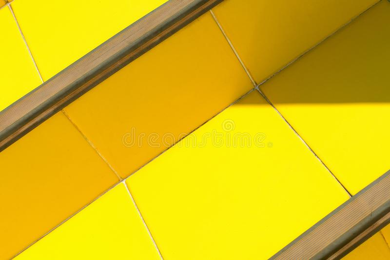 Abstract bright background - stairs of ceramic tiles of warm yellow, illuminated by the sun with darkened corners. Abstract bright background - stairs of stock images