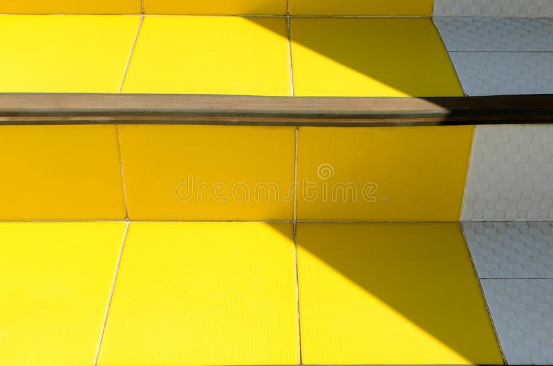 Abstract bright detail in minimal style architecture background - stairs of ceramic tiles of warm yellow. Abstract bright detail in minimal style architecture stock image