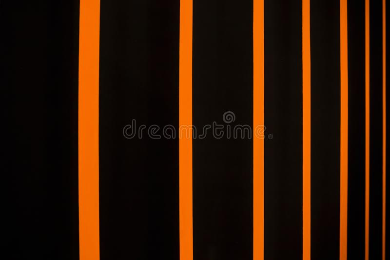 Abstract bright striped background in black and orange. Multi-colored vertical blinds royalty free stock photos