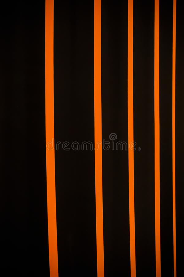 Abstract bright vertical background with stripes of black and orange. Multi-colored vertical blinds royalty free stock photo