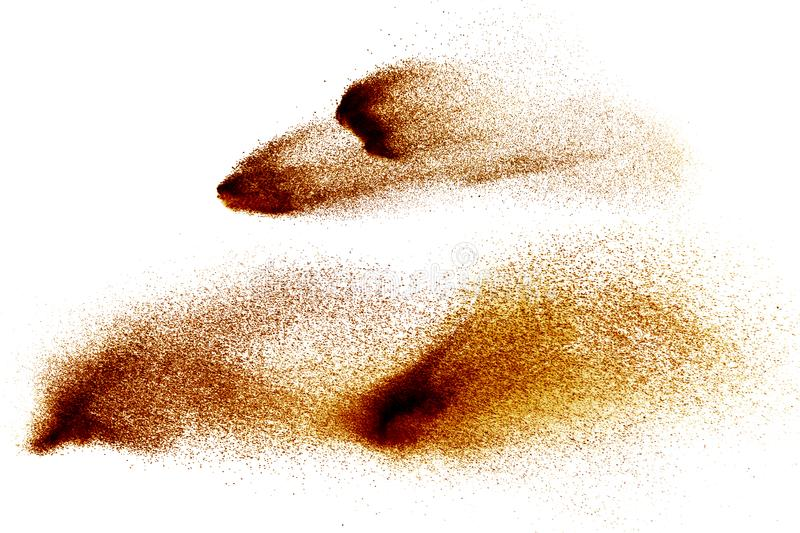 Abstract brown colored sand splash on white background. Color dust explode on background by throwing freeze stop motion royalty free stock photo