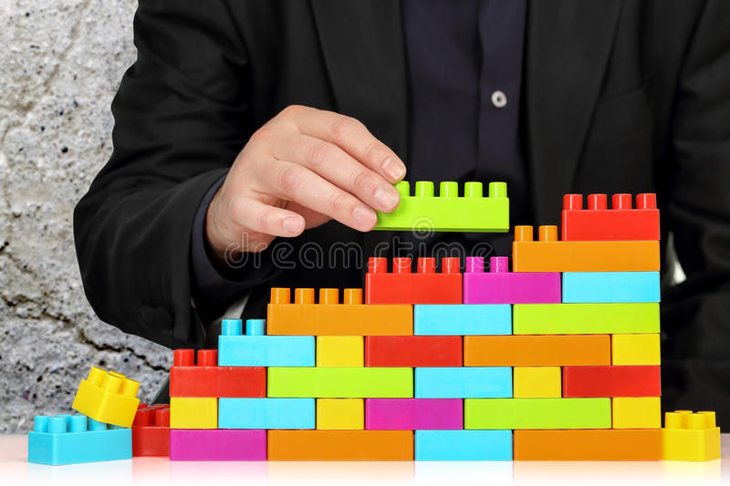 Abstract building concept. Businessman adding toy block to a wall, abstract concept royalty free stock photo