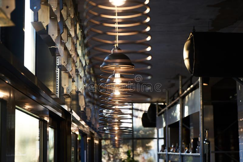Abstract cafe bar restaurant interior background with ceiling wire chandelier lamps. And light bulbs and bar counter with alcohol drink bottles royalty free stock photo