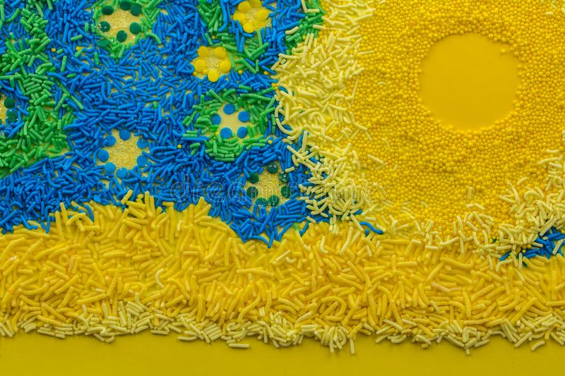 Abstract cake topping sprinkle background with conceptual picture consisting of yellow, blue and green sprinkles close up - top royalty free stock image