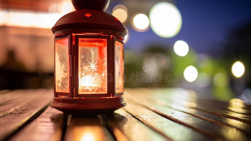 Abstract candle lantern light on wood table in blur bokeh pub re stock images