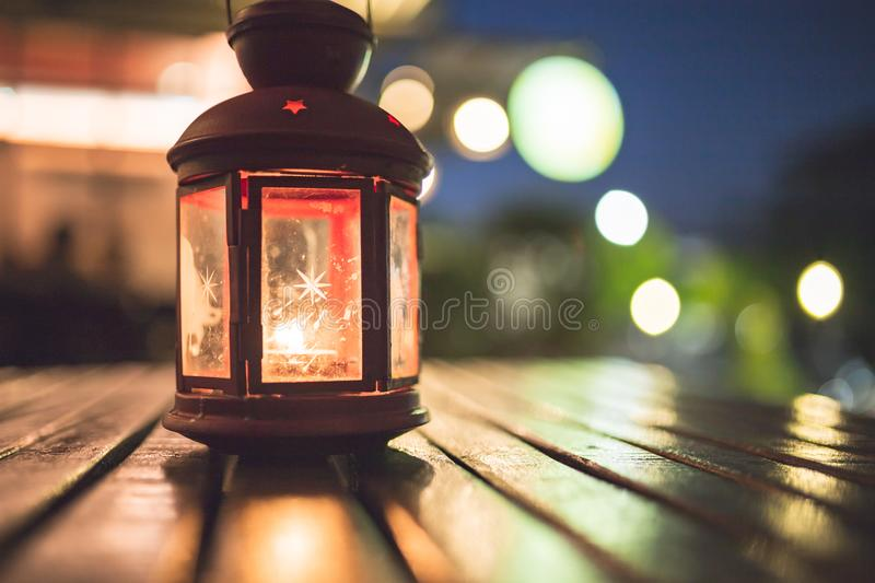 Abstract candle lantern light on wood table in blur bokeh pub re royalty free stock images