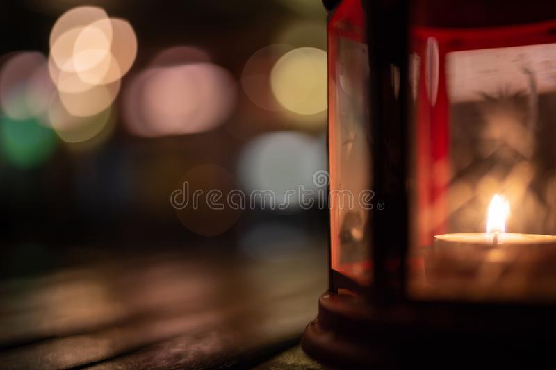Abstract candle lantern light on wood table in blur bokeh pub re royalty free stock photography