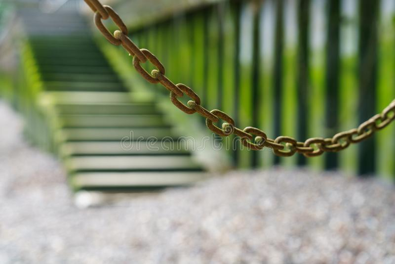 Abstract chain hanging in front of steps along the Thames at low tide, Central London royalty free stock photo